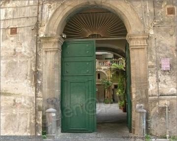 palazzo antico con portone semi aperto su androne
